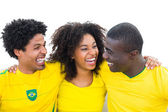 Happy brazilian football fans in yellow smiling at each other — Stock Photo