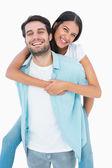 Happy casual man giving pretty girlfriend piggy back — Stock Photo