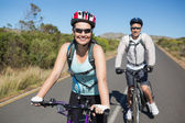 Fit happy couple going for a bike ride in the countryside — Stock Photo