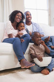 Happy family sitting on couch together watching tv — Stock Photo