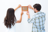 Happy young couple putting up picture frame — Photo