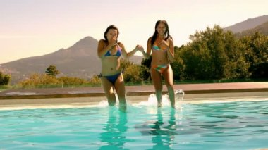 Cute friends jumping into swimming pool — Stock Video