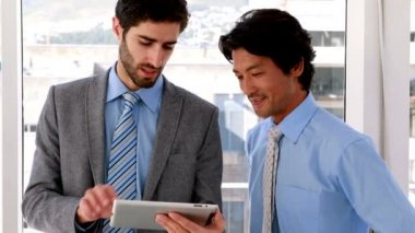 Businessman using tablet pc with his colleague — Stock Video