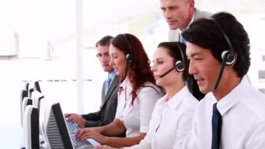 Call centre agents working and talking on headsets — Stock Video