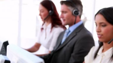 Call centre agents working and talking on headsets — 图库视频影像