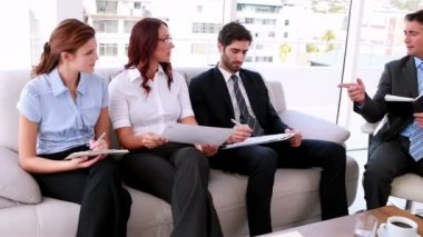 Business team sitting on couch having a meeting — Stockvideo