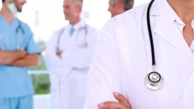 Médecin souriant à la caméra avec l'équipe derrière elle — Vidéo