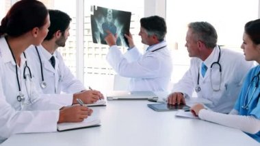 Medical team looking at x-ray during a meeting — Stockvideo