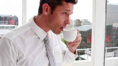 Handsome businessman drinking coffee and looking out window — Stok video