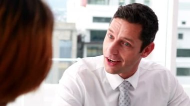 Handsome businessman talking with colleague at desk — Vídeo de stock