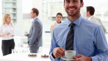 Businessman standing and drinking a coffee with colleagues behind — Stock Video