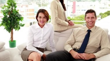 Business people sitting on couch smiling at camera — Vídeo de stock