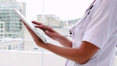 Nurse in tunic using tablet pc — Stock Video