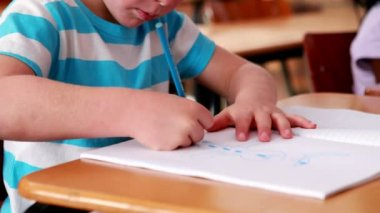 Little boy colouring in the classroom — Vídeo Stock