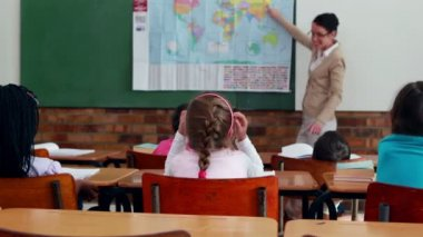 Little children listening to teacher showing the map in classroom — Stock Video