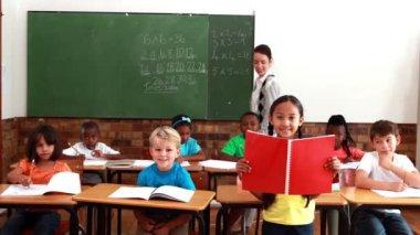 Teacher and pupils all smiling at camera during class — Vídeo de stock