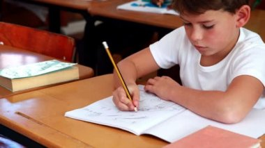 Little boy drawing in notepad in classroom — Vídeo Stock