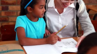 Teacher helping a little girl during class — Vidéo