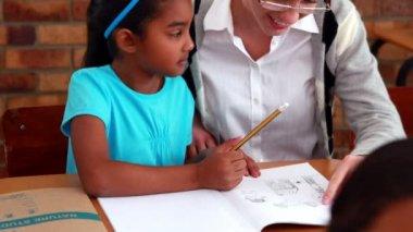 Teacher helping a little girl during class — Stock Video