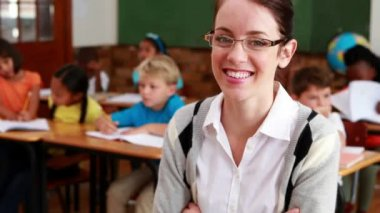 Pretty teacher smiling at camera at top of classroom — Vídeo Stock