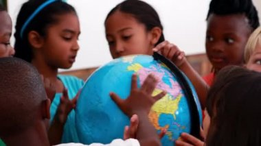 Pupils looking at the globe in classroom — Stock Video