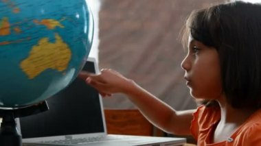 Girl looking at globe in classroom — Stock Video