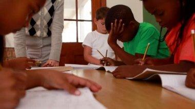 Pupils all working in classroom — Vídeo de stock