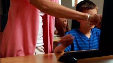 Teacher helping boy in computer class — Vidéo