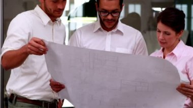 Team of architects going over blueprints — Stockvideo