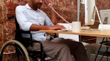 Businessman in wheelchair working at his desk — Stock Video