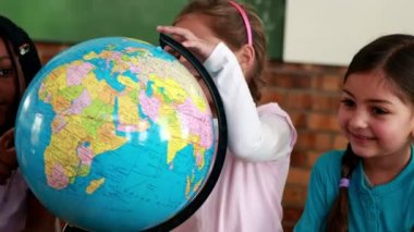 Pupils smiling around a globe in classroom — Stock Video