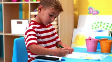 Boy colouring in classroom — Stock Video