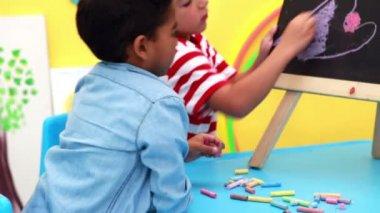 Boys drawing on mini chalkboard — Vídeo de stock
