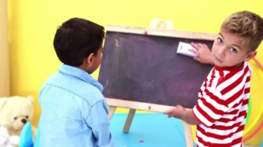 Boys wiping and knocking over mini chalkboard — Video Stock