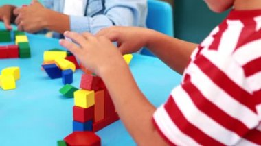 Boys playing with building blocks at table — Stockvideo
