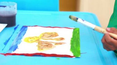 Boy painting at table in classroom — Stock Video