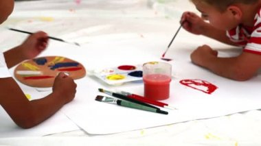 Boys painting lying on paper — Stok video