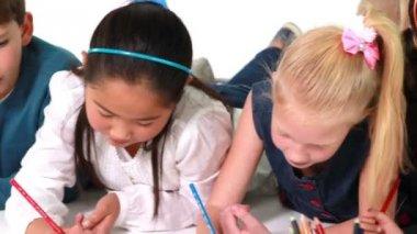 Children lying on floor drawing on paper — Stock Video