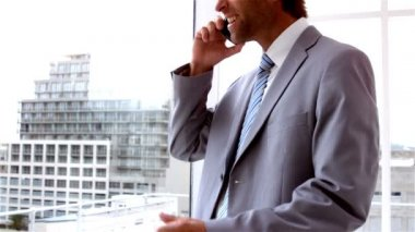 Businessman looking out window talking on phone — Stock Video