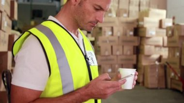 Warehouse worker sending a text on his break — Video Stock