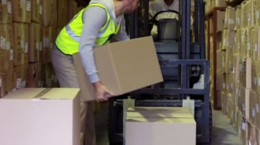 Warehouse worker packing boxes on forklift — Stock Video