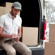 Delivery driver checking his list on clipboard — Stock Video #50533449