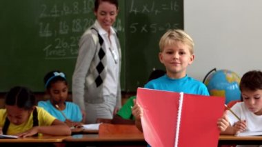 Boy holding red notepad in classroom — Stock Video