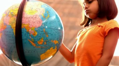 Little girl looking at globe in classroom — Stock Video