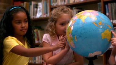 Girls looking at globe in library — Stock Video