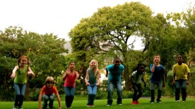 Pupils jumping on the grass outside school — Vídeo de stock