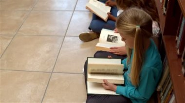 Pupils sitting on library reading books — Stock Video