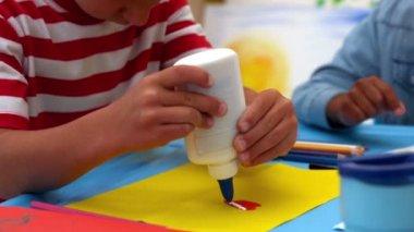 Boy using glue in classroom — Stock Video