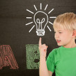 Boy pointing against blackboard — Stock Photo #51559473