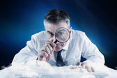 Businessman examining with magnifying — Stockfoto